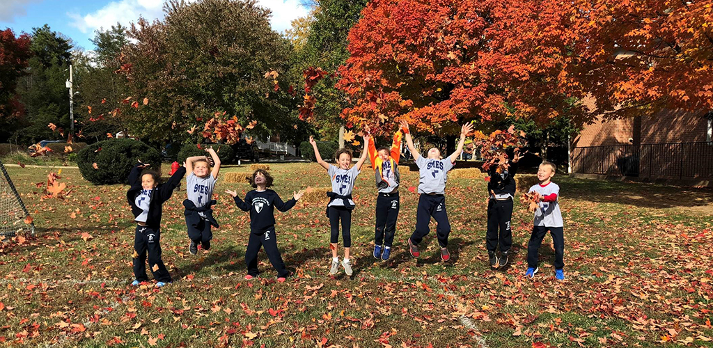 Episcopal School Kids Playing in Fall Leaves